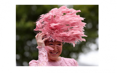 A Female racegoer during Ladies Day adorned a beautifully extravagant pink feather headpiece but got caught up in the wind. Glorious Goodwood 2017. Photo by PA - Press Association.